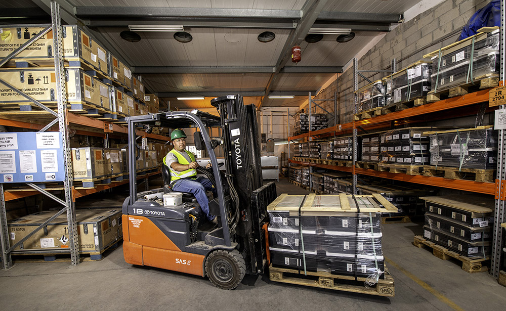 Working on a forklift in a warehouse